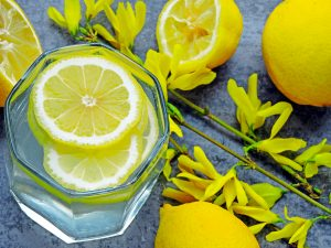 Detox water with lemon juice. Lemon water. Yellow flowers on the branches. Water with lemon wedges. The concept of cleansing the body with lemon water.