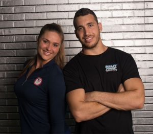 Adan and Eva Lopez from BulletProof Athletics standing in front of a black brick wall