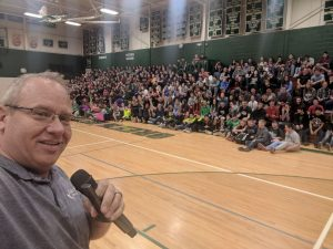 Michael DeLeon holding a microphone in a school gym with students in the bleachers