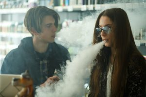 Vape teenagers. Young cute girl in sunglasses and young handsome guy smoke an electronic cigarettes in the vape bar. Bad habit that is harmful to health. Vaping activity. Black and white.