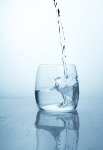 A stream of water flowing into a transparent glass cup with a splash of drops and drops. A jet of clean drinking cold refreshing spring water pouring into a glass