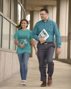 Darren Tessitore and daughter walking down hallway carrying Drug Free World materials