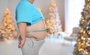 Overweight man measuring his waist in room with Christmas trees after holidays, closeup