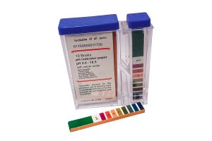 Closeup of a box of pH indicator test strips on a white background. pH-indicatorstrips, not bleeding. pH 0-14 universal indicator.