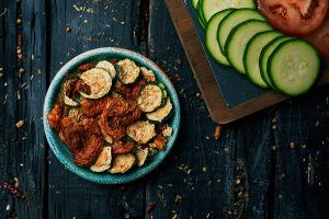 high angle view of a rustic green plate with some slices of dried tomato and zucchini, served as appetizer or snack, and some slices of raw tomato and zucchini, on a dark gray rustic wooden surface