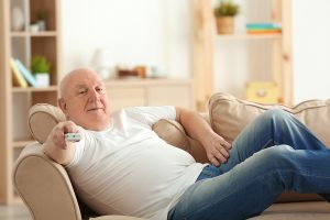 Fat senior man watching TV while lying on sofa at home. Sedentary lifestyle concept