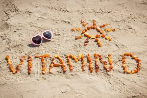 Sunglasses, inscription vitamin D and shape of sun made of amber stones at beach, concept of vacation time and prevention of vitamin D deficiency
